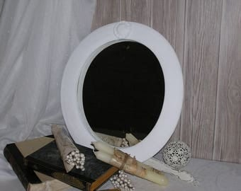 Oval mirror in white frame with an ornament