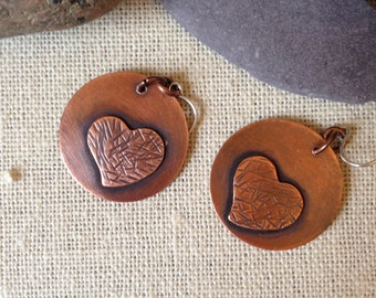 Round copper earrings with a copper heart accent