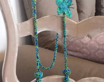 Beautiful handmade necklace with tassel of beads and butterfly. Blue