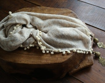 White scarf with pom poms and copper 'the hand' medallions