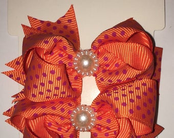 Orange and pink polka dot shoe bows that come with a magnetic snap to attach to SASSAFLATS shoes they can also be worn in the hair