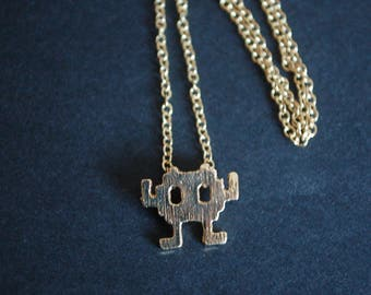 Gold tone space invaders necklace