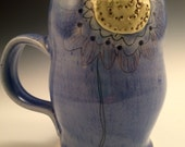Tall blue coffee mug. This mug is handmade out of porcelain and has a colored porcelain sprig on both the front and back.