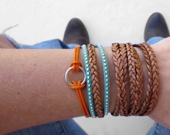 set of leather braided bracelets in boho orange, turquoise, and brown with lobster clasp chain closure. infinity circle charm.