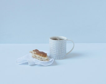 Porcelain tea or coffee cup / mug with blue running stitch pattern