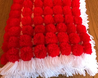 Red and white pom pom baby blanket