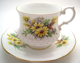 Royal Minster Tea Cup & Saucer, White embossed tea cup and saucer with yellow daisies.