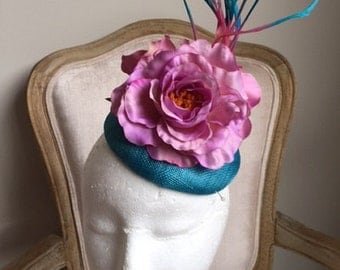 Stunning green loop fascinator with feathers and netting on a metal headband.
