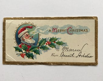 """Vintage Embossed """"A Merry Christmas"""" Gift Tag with the Image of Santa Smoking A Pipe"""