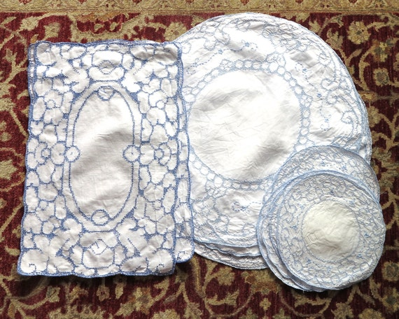 12 pieces of vintage blue on white embroidered table linen, 2 large rectangles, 3 large circles, 7 smaller circles, cut work, cross stitches