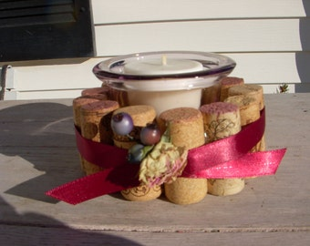 Wine cork candle ring made form a variety of winery corks then tied satin ribbon and a dried rose added.