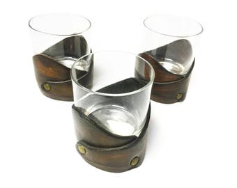 Set of three vintage drinking glasses with beautiful leather holders.