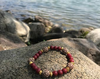 Red bracelet with flower beads and gold accents