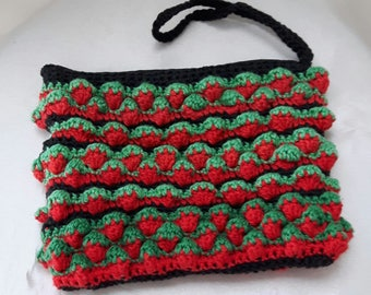 A knitted handmade clutch bag in red three-dimensional strawberry pattern with green leaves made of  100% cotton yarn