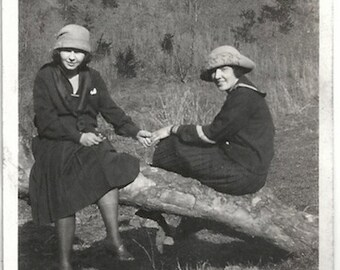 Old Photo 2 Teen Girls Hold Hands sitting on Fallen Tree wearing Skirts Hats 1920s Photograph Snapshot vintage