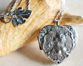 Victorian music box locket,  heart shaped locket with music box inside, in silver tone with Victorian maiden on front cover