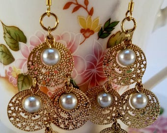 Gold and pearl dangle earrings.