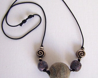 Beautiful piece of jewelery which is made in gray and stone tones. Is light in wearing.