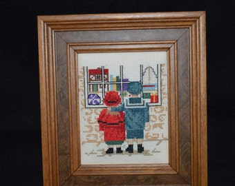 Cross stitch art / children / Christmas dreams / toys / window shopping / red/ blue/ wood frame / framed in wood / holiday shopping / dreams