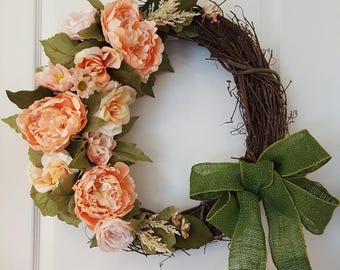 Peonies and roses in shades of peach and pink adorn this grapevine wreath, finished with a green linen bow.