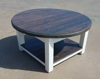 Round farmhouse coffee table with dark walnut stained top and lower shelf, and white distressed skirt and legs. Fixer upper, rustic table