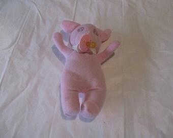 a pink pig stuffed animal holds a pacifier