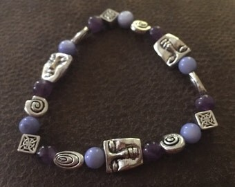 Purple glass beads with silver colored faces, celtic symbols stretchy bracelet