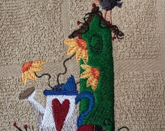 Machine embroidered towel with birdhouse, bird, watering can and flowers