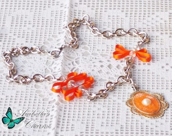 Necklace with pendant cameo made of polymer clay embellished with crystals and ribbons orange colour