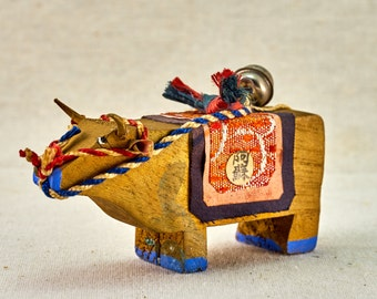 Folk style toy - wooden cow with bell and traditional ornament. Vintage, Japanese, wooden figurine.