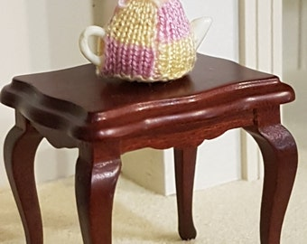 Miniature hand knitted tea cosies