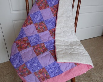 Handmade baby quilt in purples and fusia print with white floral backing.