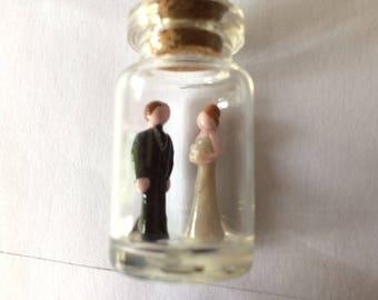 Miniature bride and groom in a jar, wedding keepsake.