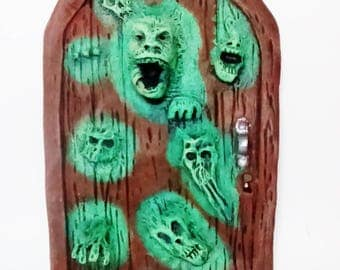 Scary Fairy Door, brown and green fairy door, 3d faces and limbs.