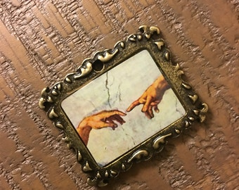 Jewelry pendant in metal with picture of hands reaching toward each other