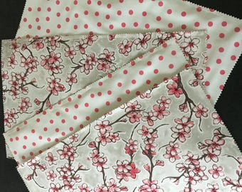 Reversible cherry blossom and pink polka dot oilcloth placemats