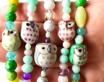 Colorful spring ceramic owl and czech glass beaded bracelets. Handcrafted jewelry in pretty pastel hues, perfect for Easter or spring gifts.