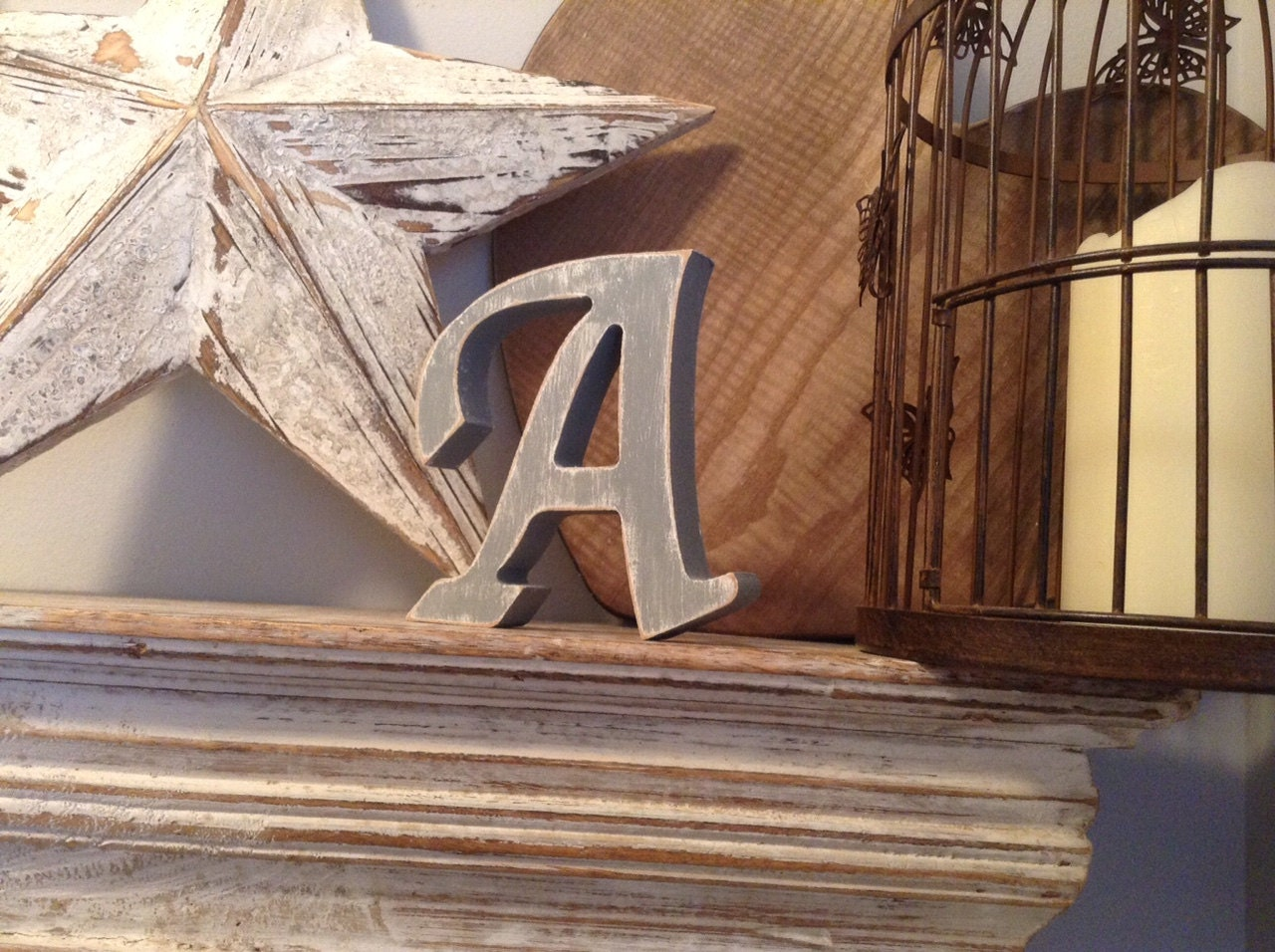 Letter A in Apple Chancery Font, painted white, with a grey over the top, and distressed