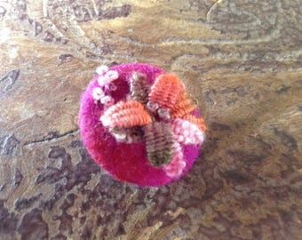 Handfelted and embroidered button.