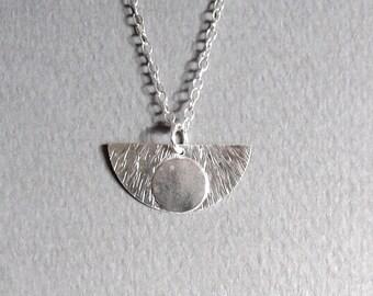 Half-disc silver pendant with smaller disc