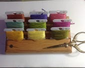 An organizer for your embroidery thread bobbins. Compactly holds 9 bobbins, your scissors and needles.