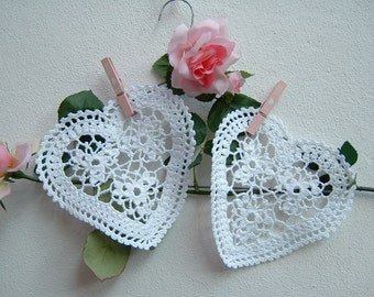 Two heart-shaped white crochet lace. Crochet House in romantic style. Lacy hearts. Decoration in white cotton.