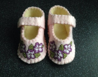 Pink felt booties with crosstitched purple &  white flowers edged with blanket stitches.