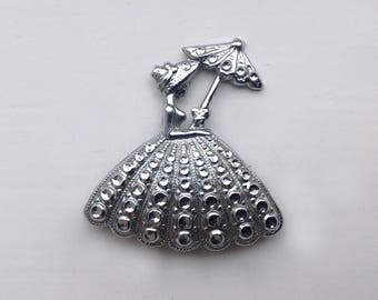 An evocative and charming 1940s/50s white chrome/metal Brooch/Pin of a girl with a parasol