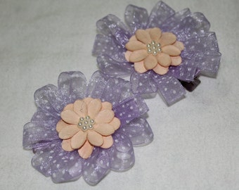 a pair of purple polka dotted ribbon with flowered center