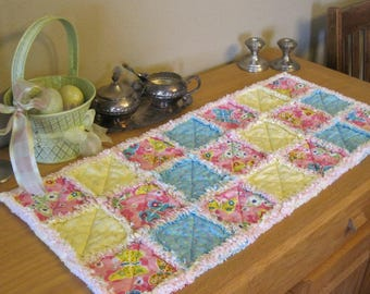 Table runner in spring colors of pink, blue and yellow. Rag quilted.