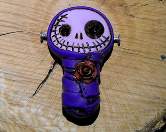 Really purple baby mummy (bandage and face). Creepy and cute skull with a red rose on his chest and metal nails. Brooch or magnet