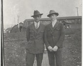 Old Photo 2 Men wearing Suits and Hats one wearing Round Glasses Building with Lettering in Background 1910s Photograph Snapshot vintage