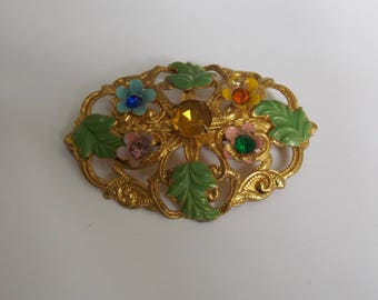 old brass brooch has floral decoration