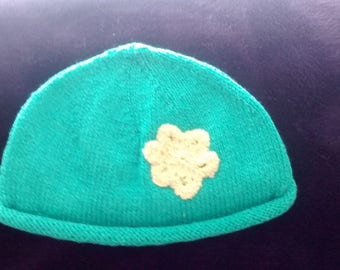 Hand knitted girls hat age 5-6. Knitted in green silky smooth washable wool with a yellow embroidered flower detail.